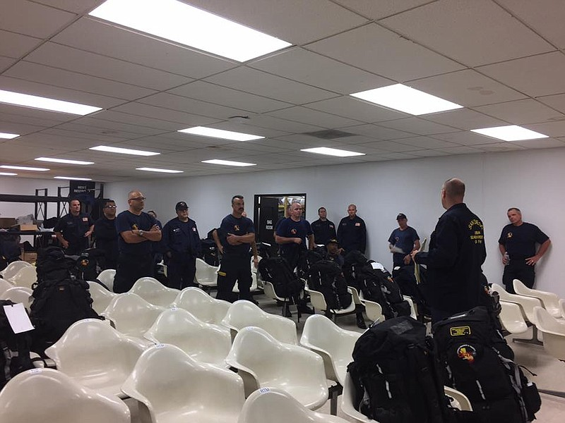 Members of the San Diego Urban Search and Rescue (CA-TF8) gear up before head...