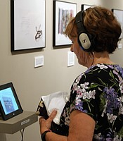 PC member listens to audio explaining the exhibit at the New Americans Museum.
