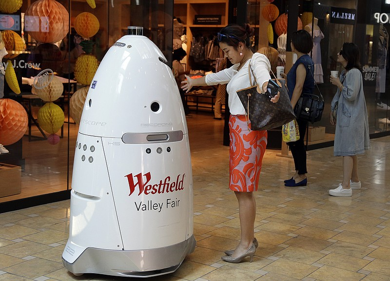 Sophie Li, of Cupertino, Calif., offers to dance with a K5 robot made by Knig...