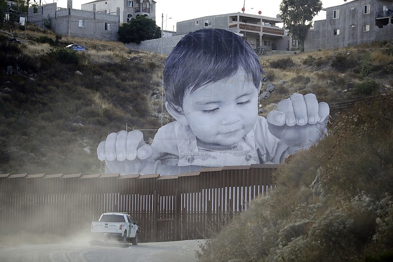 A Border Patrol vehicle drives in front of a mural in Tecate, Mexico, just be...