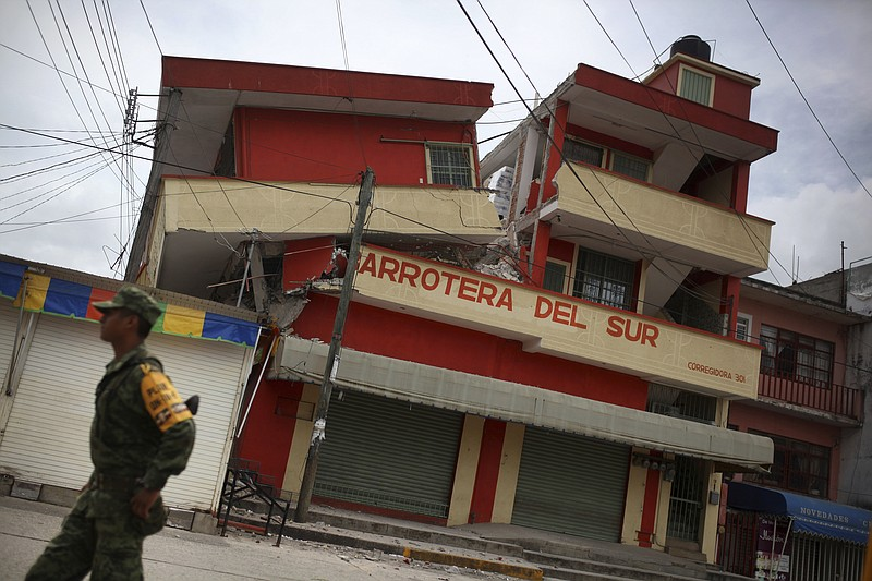 A soldier walks by a partially collapsed structure in the town of Matias Rome...
