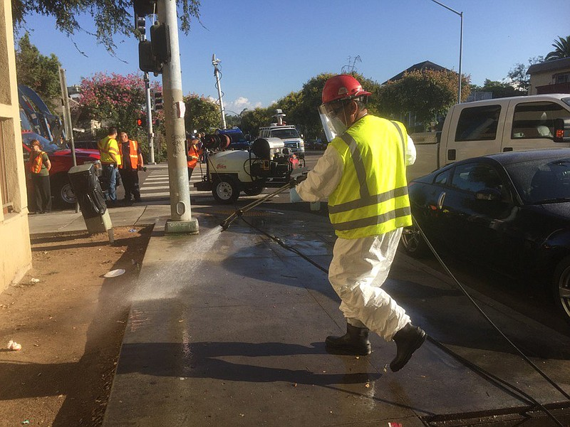 City workers wash down streets and sidewalks in an effort to control Hepatiti...