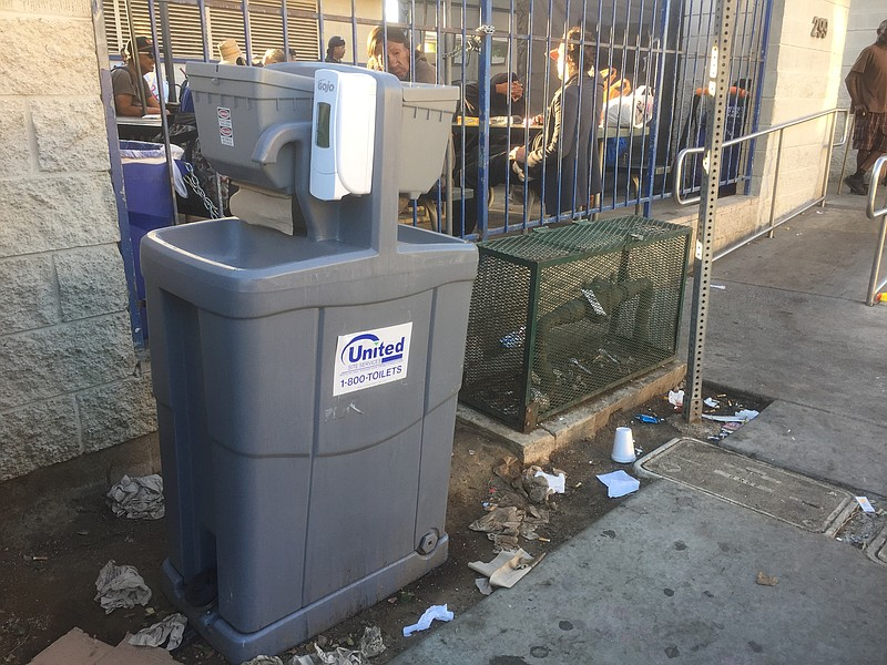A hand washing station is set up outside the gates of the Neil Good Day Cente...