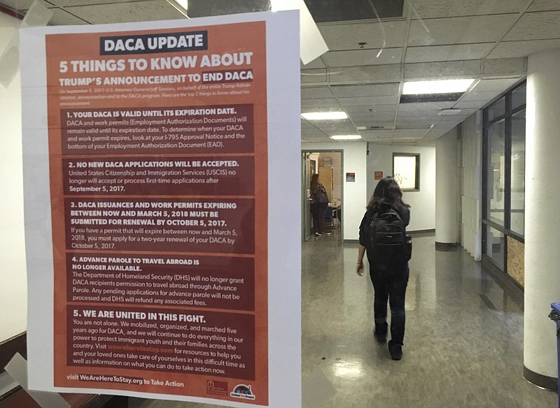A student walks past a tip sheet for Deferred Action for Childhood Arrivals r...