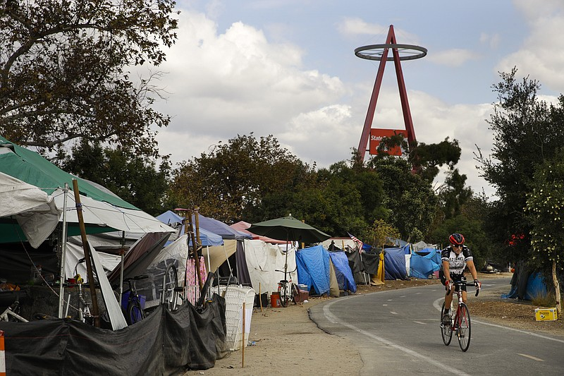 A cyclist passes the row of tents and tarps along the Santa Ana riverbed near...