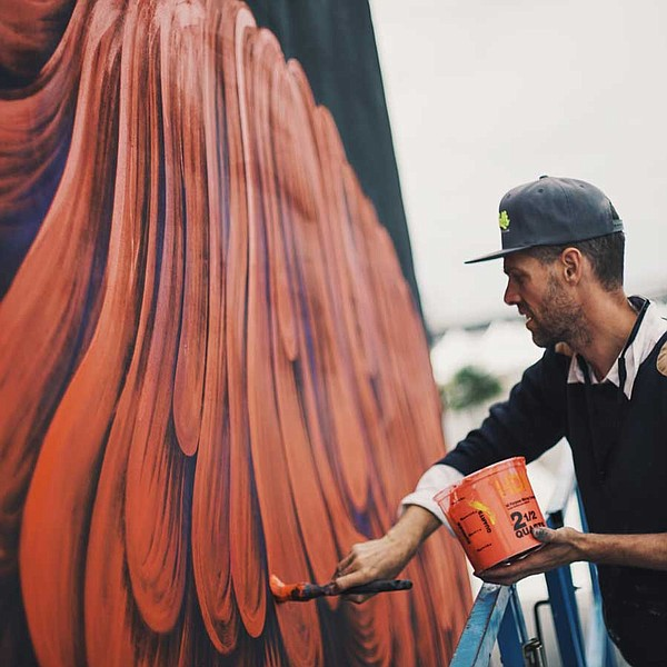 A photo of an artist painting a mural at the Kaaboo music...