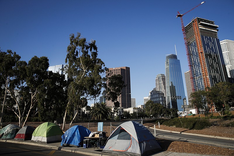 Tents housing homeless people are dwarfed by tall buildings including the Wil...