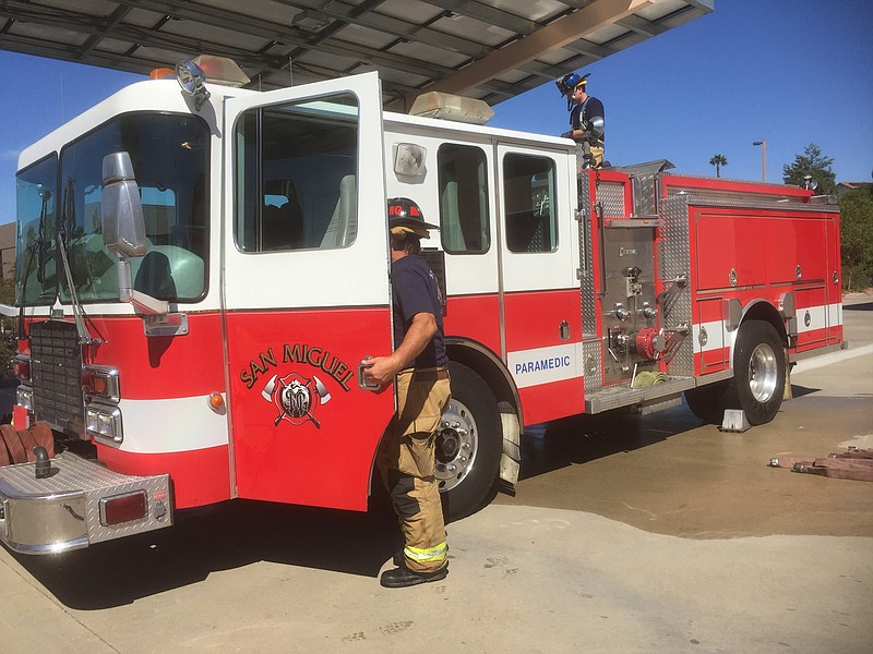 San Miguel firefighters do maintenance on a firetruck, while some of their cr...