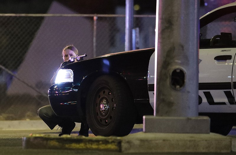 A police officer takes cover behind a police vehicle during a shooting near t...