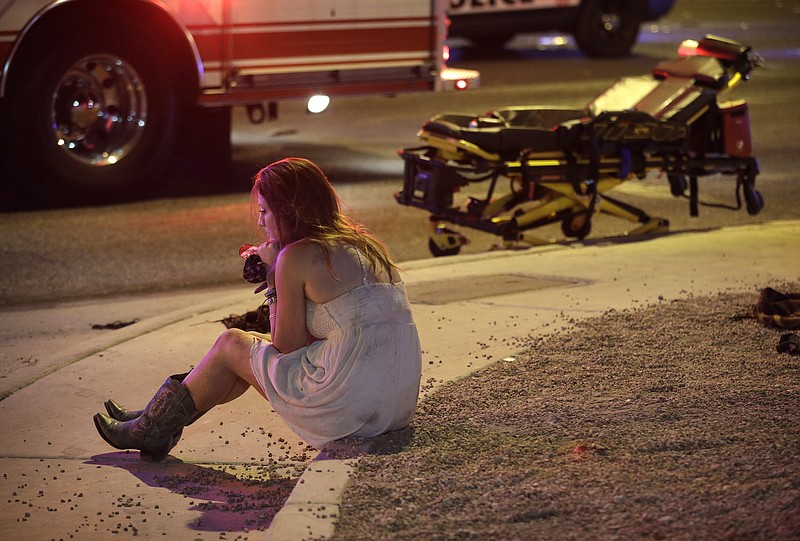 A woman sits on a curb at the scene of a shooting outside of a music festival...