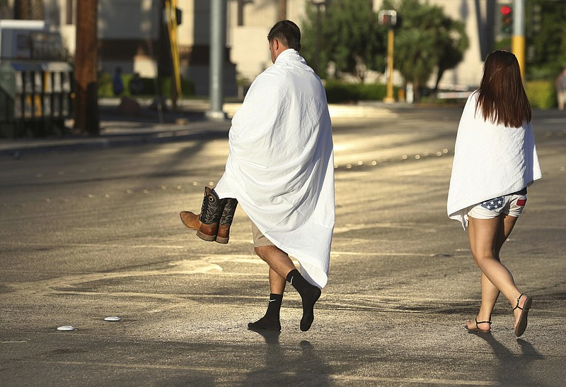 People walk near the Las Vegas Strip shortly after sunrise Monday, Oct. 2, 20...