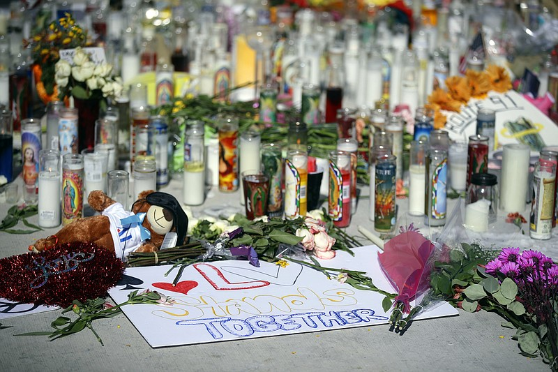 Flowers, candles and toys are left at a makeshift memorial site on Las Vegas ...