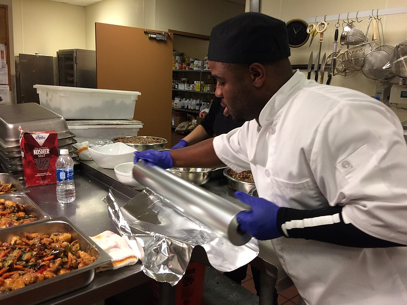 Frank Daley helps prepare meals for attendees at the Kitchens for Good gradua...