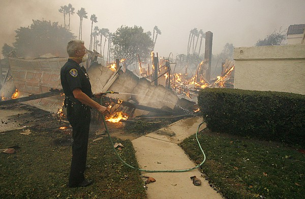 A San Diego Police officer uses a garden hose to try to s...