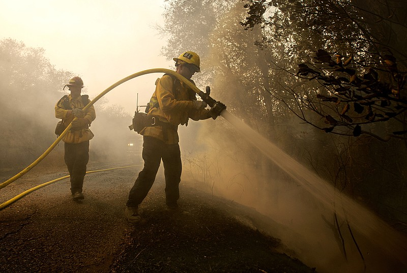 Santa Paula firefighter Tyler Zeller, right, hoses down a hot spot with the h...