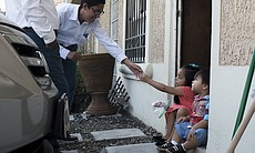 Aaron Bohorquez, 16, reaches for a piece of candy from his 6-year-old sister,...