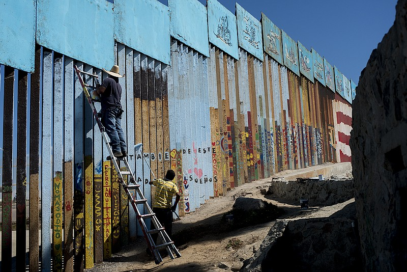 Enrique Chiu stands on a ladder to paint the U.S.-Mexico border fencing at Fr...