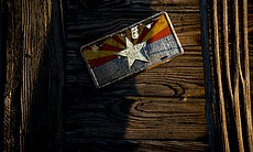 An Arizona license plate is nailed to the wall of a small barn outside Ajo, A...