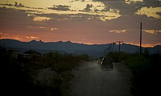 Trucks and SUVs leave a camp outside Ajo, Arizo...
