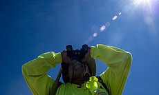 Ely Ortiz peers through his binoculars while scanning the desert along the U....