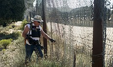 Bob Maupin, 78, checks an area of fencing along...