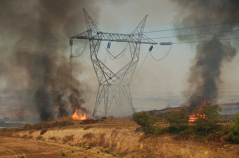 A fire burns near a power line in Rancho Bernardo, October 2007.
