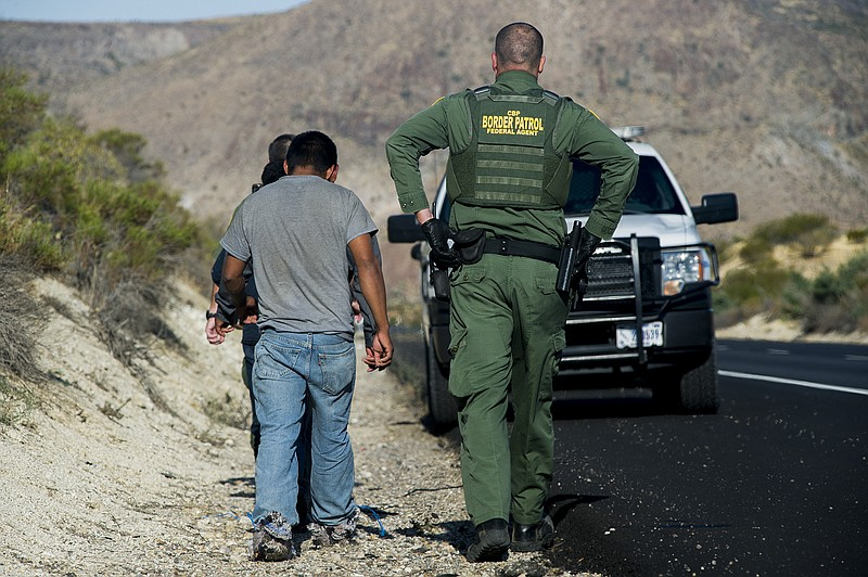 A Border Patrol agent detains three men along Interstate 8 near the U.S.-Mexi...