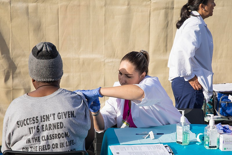 A person receives a vaccine at a homeless campground, Oct. 9, 2017.