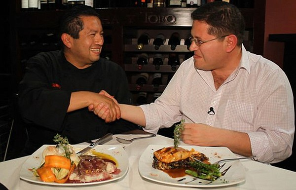 Host Jorge Meraz (right) samples food from Mujeres Divinas Restaurant.