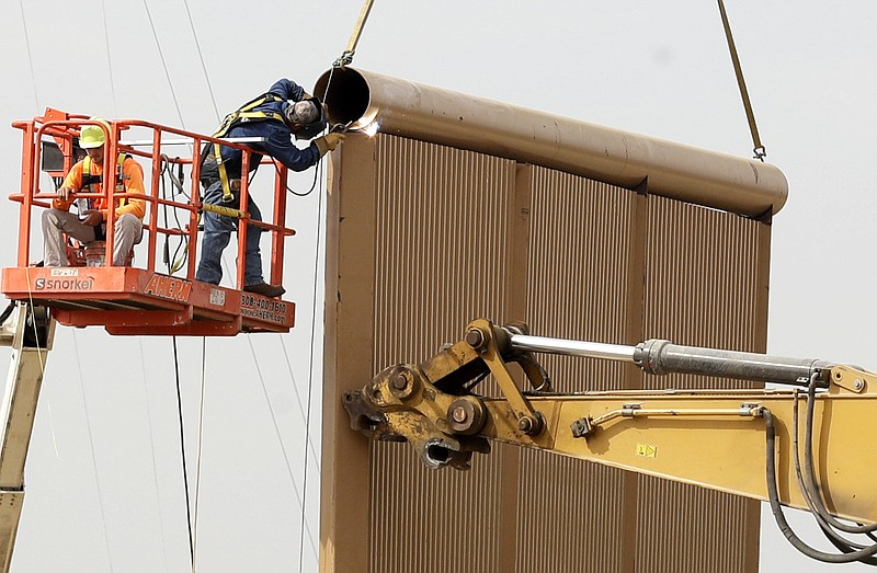 Crews work on a border wall prototype near the border with Tijuana, Mexico in...
