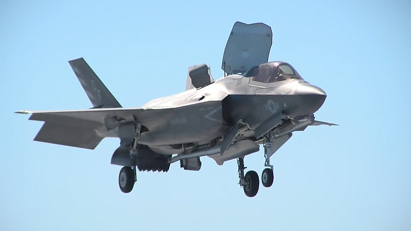 A Marine version of the F-35 Joint Strike Fighter hovers over the deck of the...