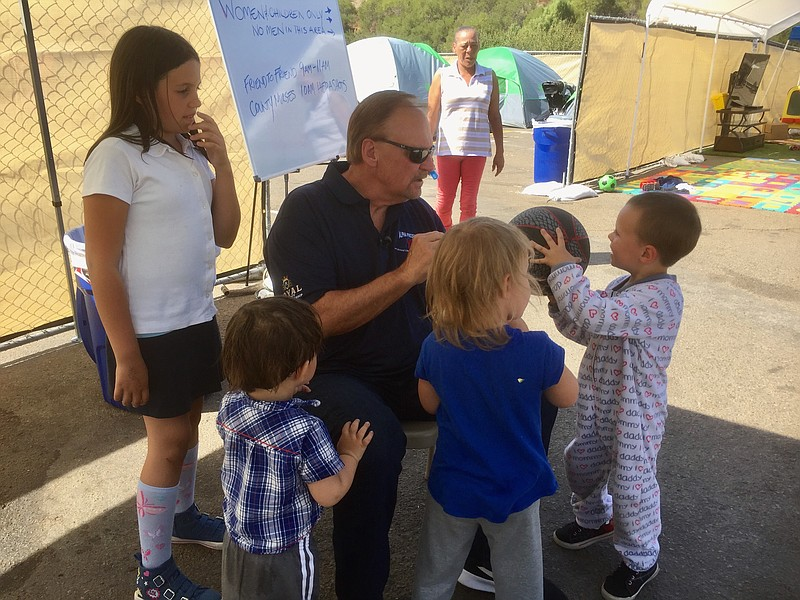 Bob McElroy, CEO of the Alpha Project, talks to children at the homeless tran...