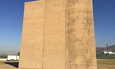 (1) A border wall prototype stands by the U.S.-...