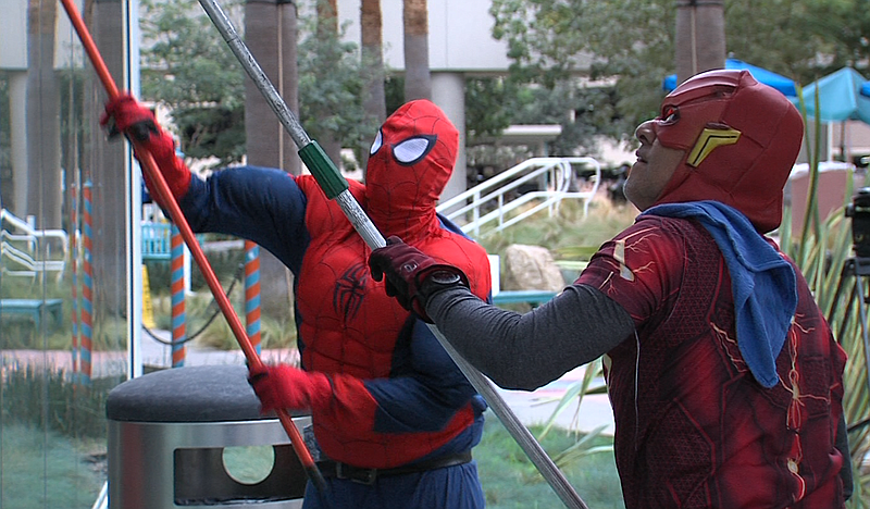 Window washers dressed up as superheroes for Halloween wash windows at Rady C...