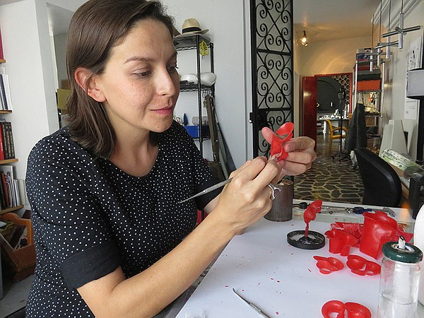 Carmen Tapia carves and shapes the wax pieces for molding.