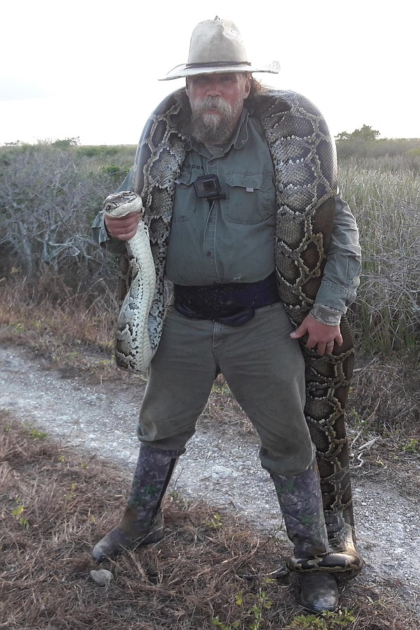 Thomas Rahill poses with a python in this undated photo.