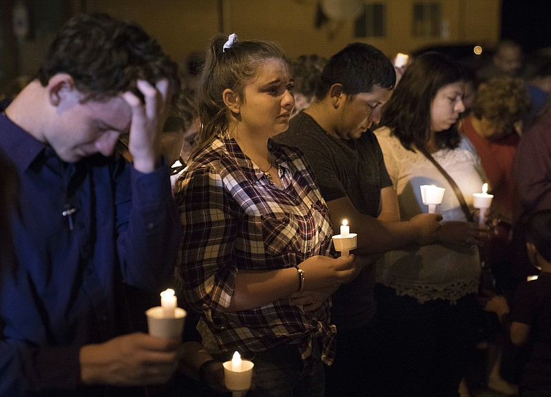 Mourners participate in a candlelight vigil held for the victims of a fatal s...