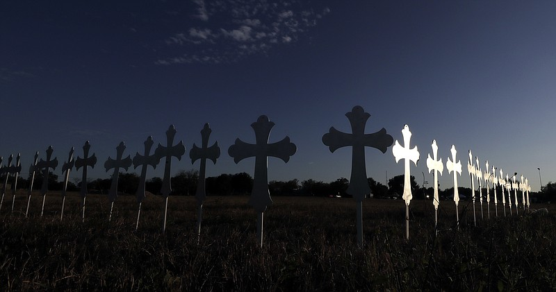 The sun is reflected on some of the 26 crosses placed in a field before a vig...