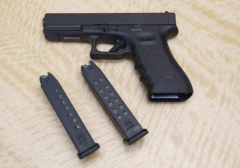 A semi-automatic hand gun is displayed with a 10 shot magazine, left, and a 1...