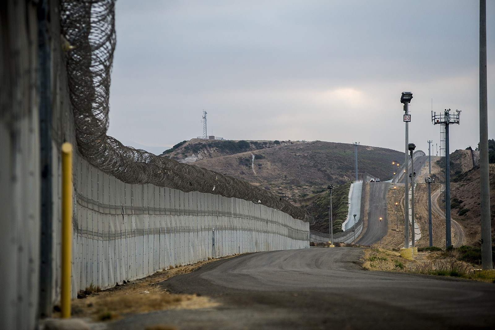 Stretches of secondary fencing are topped with spirals of concertina wire alo...