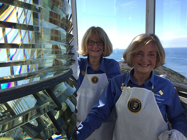 Twin sisters Kim Fahlen (left) and Karen Scanlon clean the Fresnel lens in th...