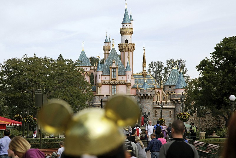Visitors walk toward Sleeping Beauty's Castle in the background at Disneyland...