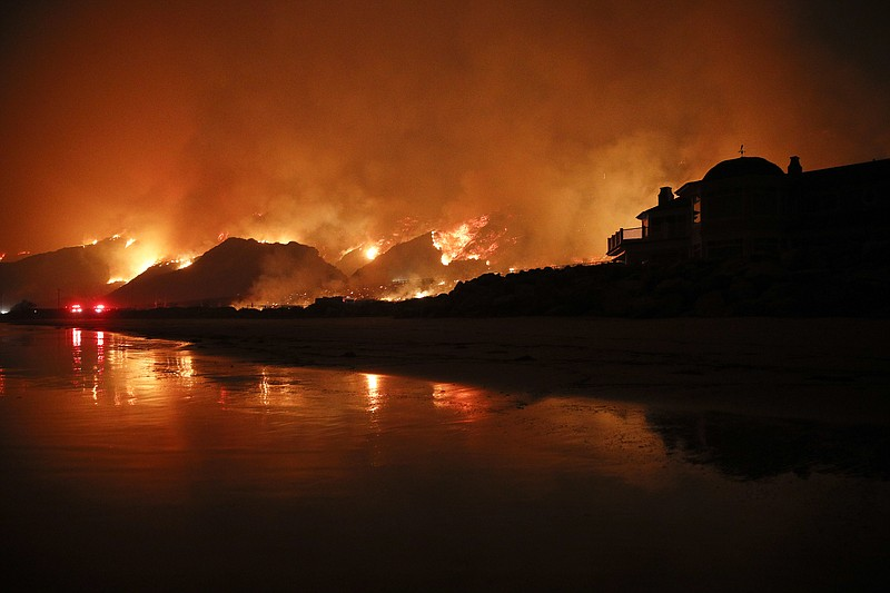A wildfire burns along the 101 Freeway in Ventura, Calif., Tuesday, Dec. 5, 2...