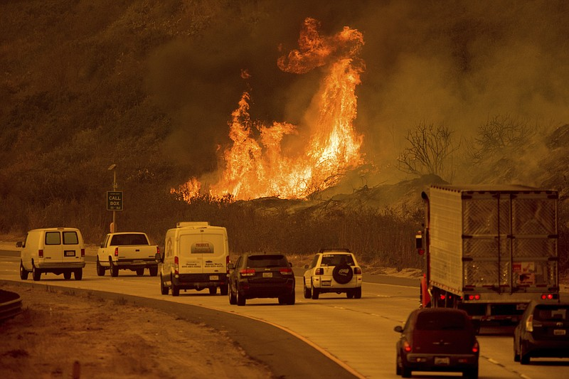 Flames from a wildfire leap above traffic on Highway 101 north of Ventura, Ca...