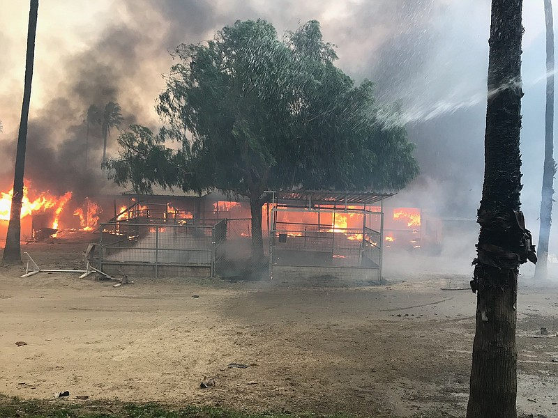 Flames from the Lilac fire in San Diego's North County destroy a structure wh...