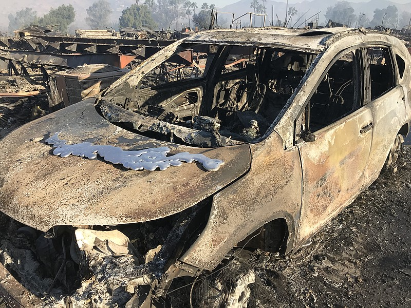 A car burned in the Lilac Fire sits in the neighborhood of the Rancho Monser...