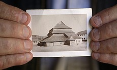 Rick Brown holds the photo of Gwozdziec synagog...