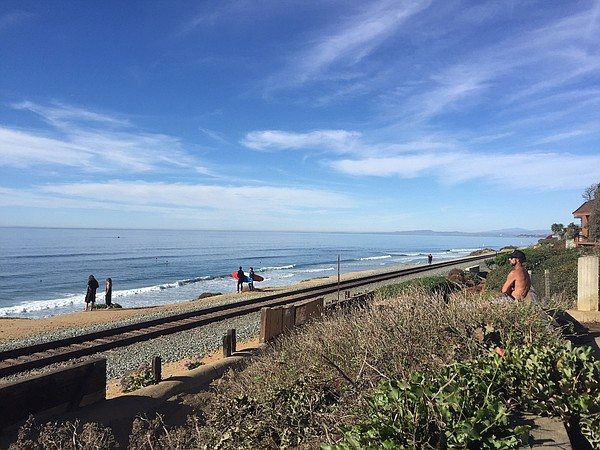 Pedestrians cross the train tracks in Del Mar to get to t...