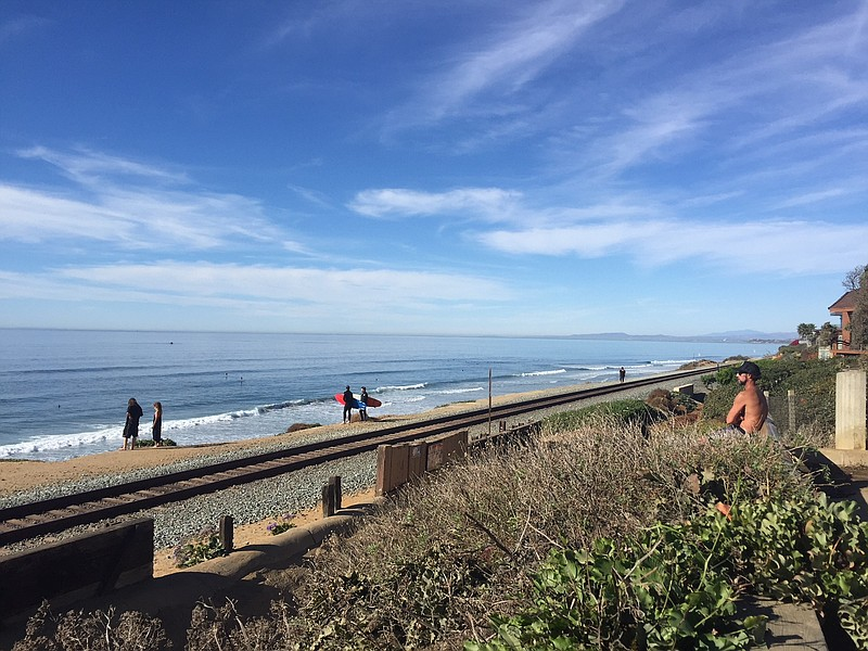 Pedestrians cross the train tracks in Del Mar to get to the beach, Dec. 11, 2...