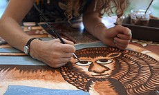 Emily White paints the lion for the east dome p...